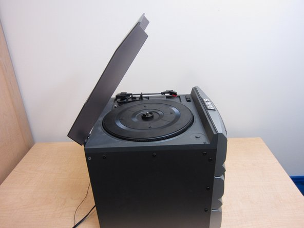 Open the lid to access the turntable, arm, and stylus.