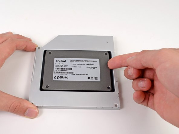 While firmly holding the enclosure in place with one hand, use your other hand to press the hard drive into the enclosure connectors.