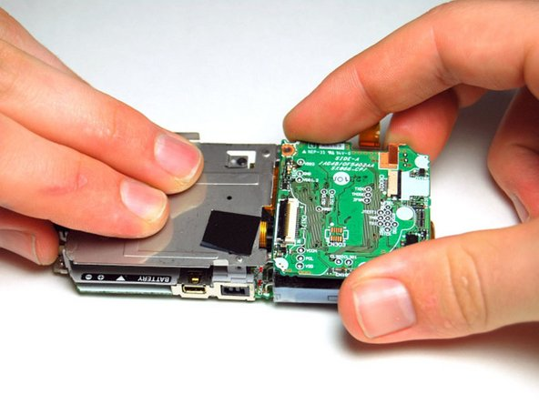 Press down on the metal plate and gently lift the motherboard up from left to right.