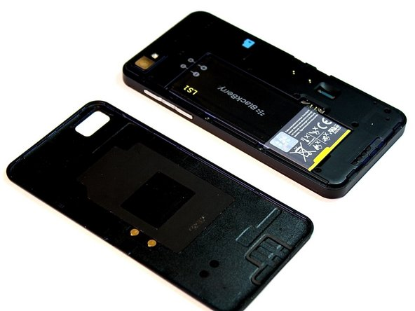 Image 2/2: Start from the bottom and work your fingers up along the sides of the phone until the back cover is completely separated from the body of the phone.