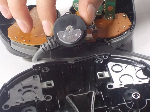 Next, remove the rumble motor by unscrewing the 2 screws connecting it.