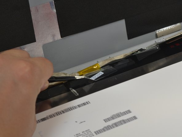 Use the blunt nose tweezers to peel up the adhesive on the display cable.