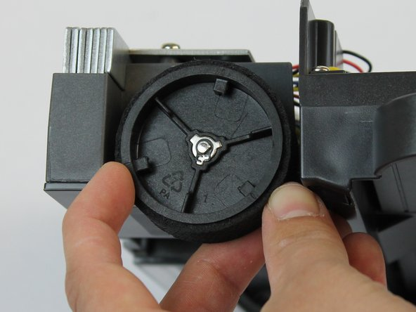 Using a small Flathead screwdriver, remove the small black clip in the center of the wheel.