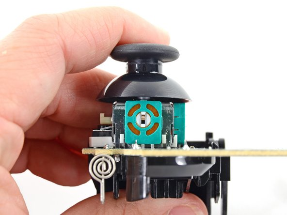 On the lower PCB, we get a good look at one of  the two analog joysticks. Its spring-loaded movement is tracked by two potentiometers that measure degrees of tilt in two axes.