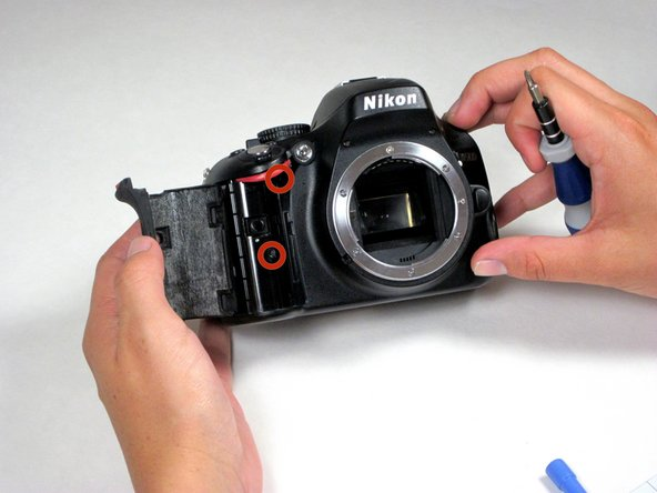 Carefully peel back the rubber hand grip, which is attached to the camera body with strong adhesive.
