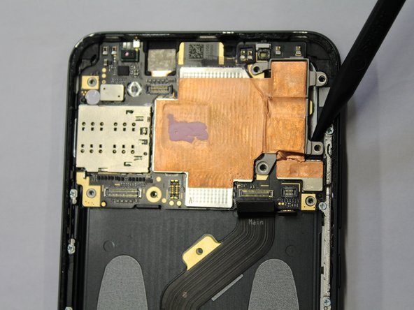 Using the pointed end of plastic spudger, pry the motherboard away from the back housing.