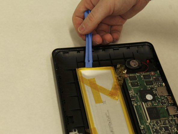 To remove the battery, use the plastic opening tool to pry one corner off of the battery and gently move the opening tool down to pull up one side of the battery.