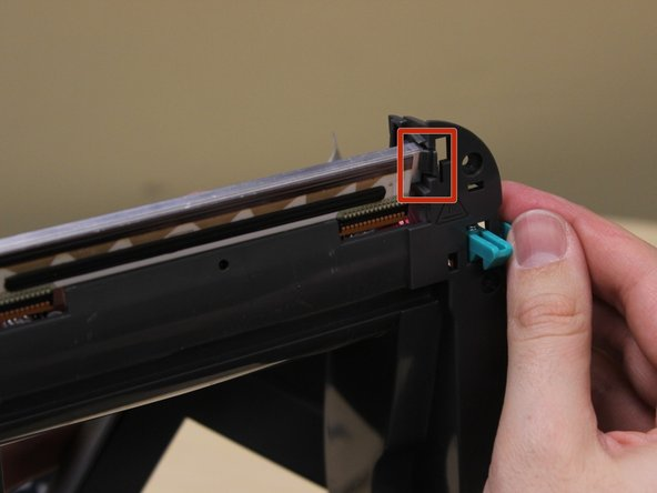 Press the plastic tab holding the printhead in place.