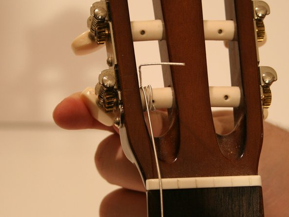 As you tighten the string, be sure to hold the string with your free hand until the string stays tight on its own. This will keep the knot from loosening.