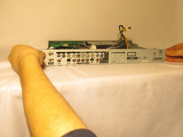 Grab the sides of the back panel and remove it from the DVD player.