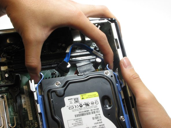 Image 1/1: Then slide the hard drive out of the computer while squeezing the tabs.
