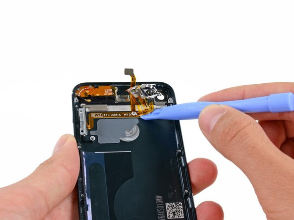 Image 1/3: Slide a plastic opening tool from right to left underneath the horizontal section of the cable, separating it from the adhesive securing it to the rear case.