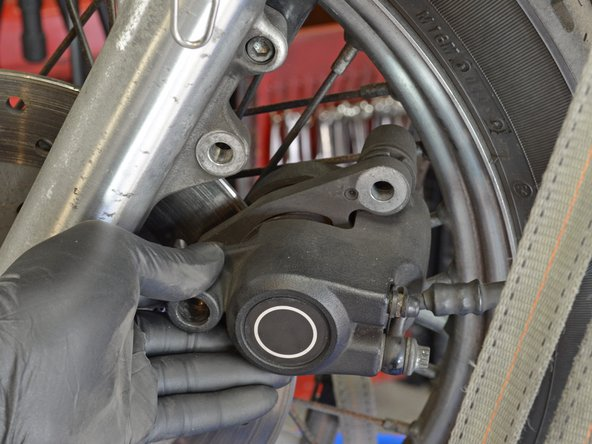 Carefully slide the brake off of the brake rotor and hang it from the metal hanger.