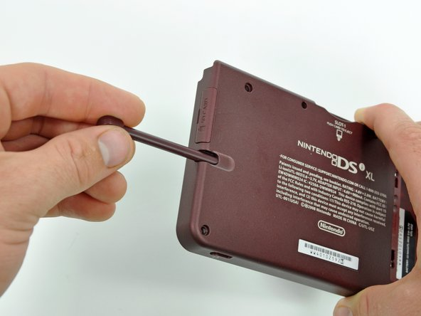 Remove the stylus from its housing on the right side of the DSi XL.