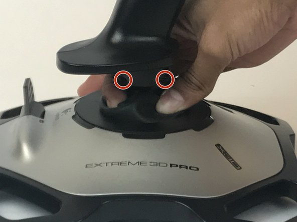 Using your fingers, lower the rubber boot to reveal two screws underneath the joystick.