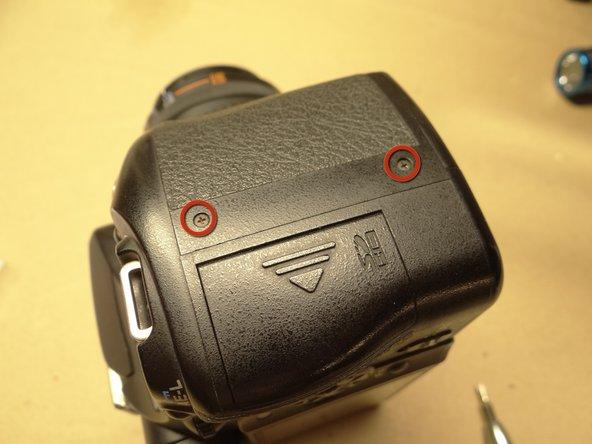 フロントカバー右部とカメラボディを固定する2本のネジ(4.3 mmプラスネジ) を取り外します。
