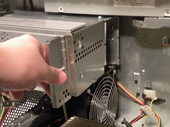 Start removing the optical drive cage by removing the back cover.