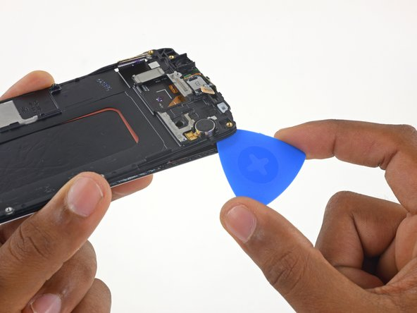 Use just the tip of the pick for this step, as the touchscreen controller IC is below the display frame in the top right corner.