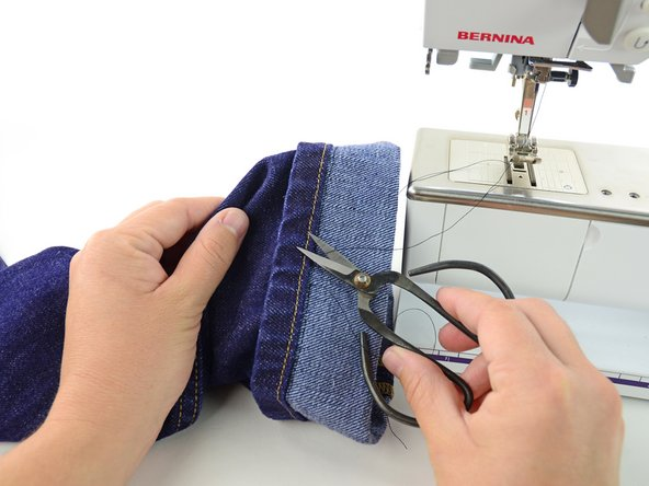 Image 1/2: Clip the threads that attach the jeans to the sewing machine.