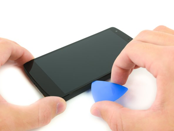 Work the opening pick along the edges of the screen to break any remaining adhesive and free the screen assembly.