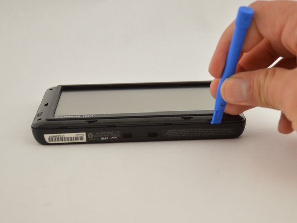 Using the plastic prying tool, dislodge the  frame from the body of the device.