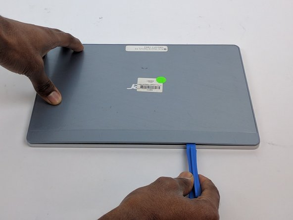 Slide the plastic opening tool along this crevice to pry apart the backing of the tablet.