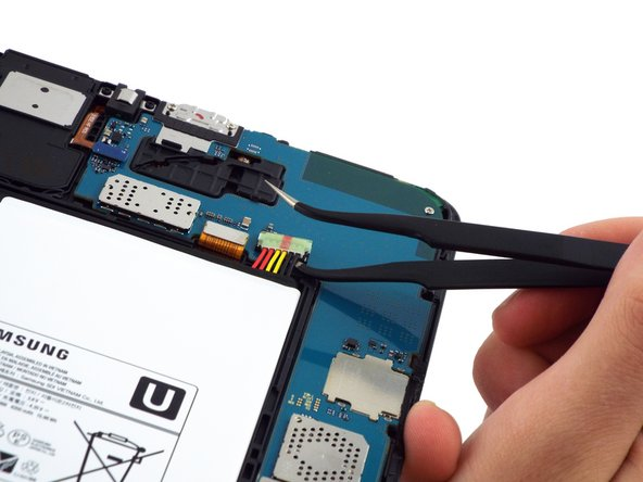 Use the bent precision tweezers to disconnect the battery connector from the  motherboard.