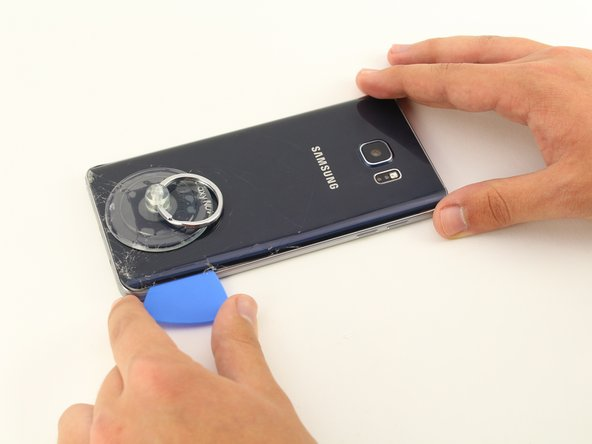 Keeping the pick under the rear glass, move the pick along the bottom edge of the device to cut the adhesive.