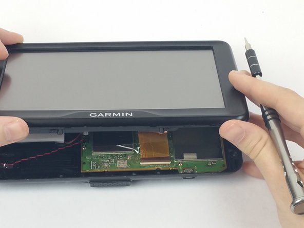 "Lift the screen opposite where the ""GARMIN"" logo is located. Remove the clear tape holding the ribbon cable to the motherboard."