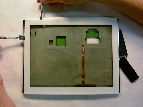 Slide the metal opening tools across the sides of the screen in order to separate the adhesive away from the screen.