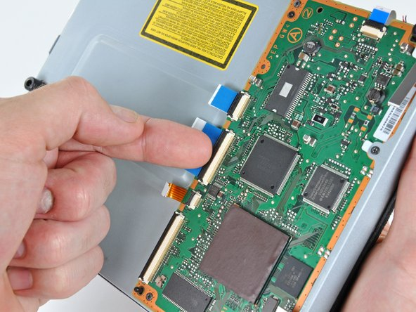 Using your fingernail, lift the flap on the ZIF connector holding the Blu-ray lens Data cable to the Blu-ray control daughterboard.