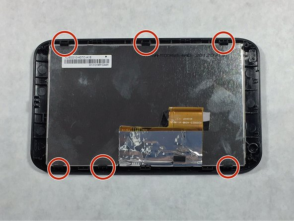 Image 2/3: Using a plastic opening tool, apply light lifting pressure to each of the 6 casing clips to release the screen from the plastic casing.