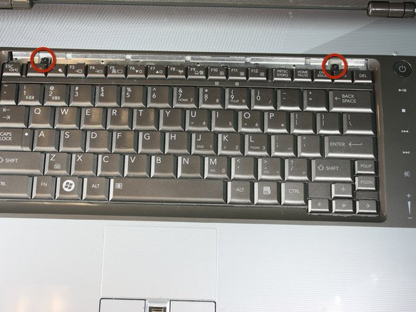 Using your Phillips #00, unscrew the two 4.80mm screws at the top of the keyboard.