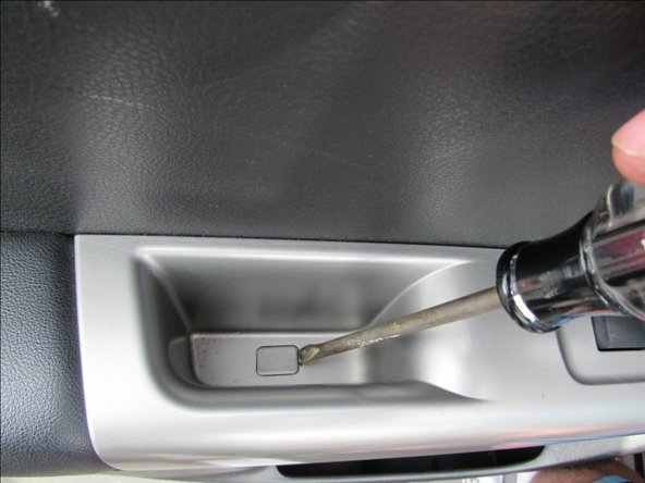 Use a flathead screwdriver to pry up the plastic tab inside the rear door armrest.