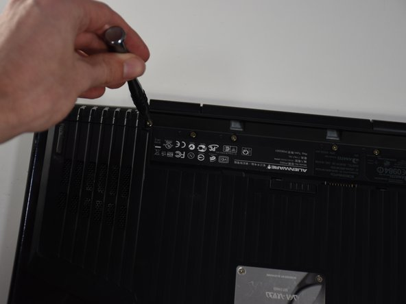 Remove the two 4-mm screws that hold the compartment door to the rest of the computer using a PH#0 screwdriver tip.