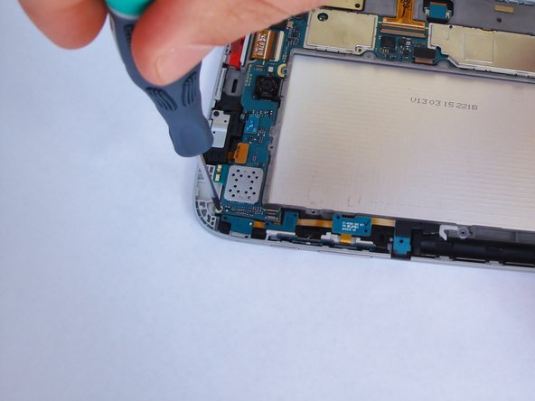 Remove the 3-mm screw holding the upper left corner of the main board using a Phillips#00 screwdriver.