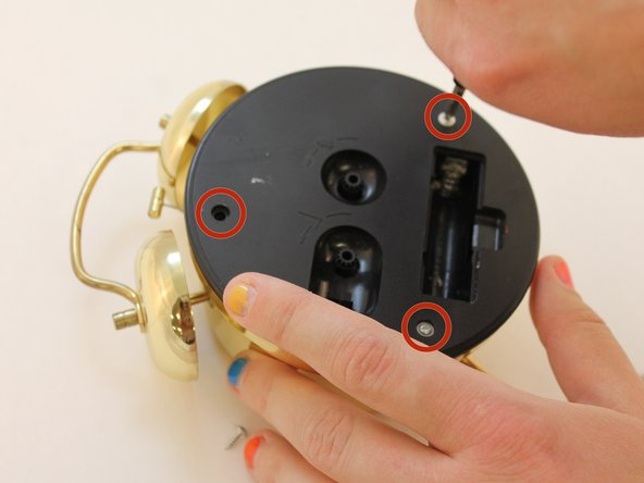 Using a Phillip's Screwdriver, remove the three screws on the back cover of the clock.