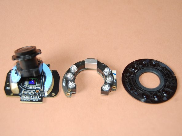 The outer ring has lenses to focus IR light, and a hole for the camera lens.