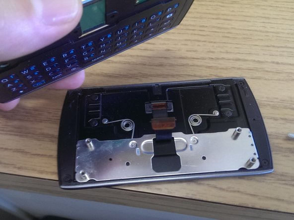 Since the screws were removed the phone's keyboard containing half can be lifted away from the screen.