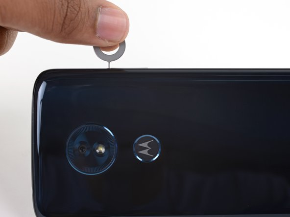 Insert a paperclip or SIM card eject tool into the small hole in the SIM card tray on the upper right edge of the phone.