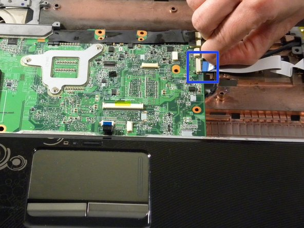 Disconnect the TouchPad cable from the system board by pulling the blue Mylar tab toward you.