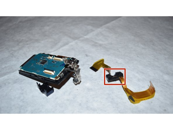 After removing the flex cable from the internal components, separate the LCD pivot arm housing from the flex cable using a spudger.
