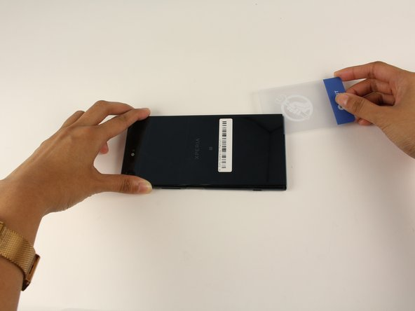Slide a thin plastic card under the back panel and around the perimeter of the phone to remove the adhesive.