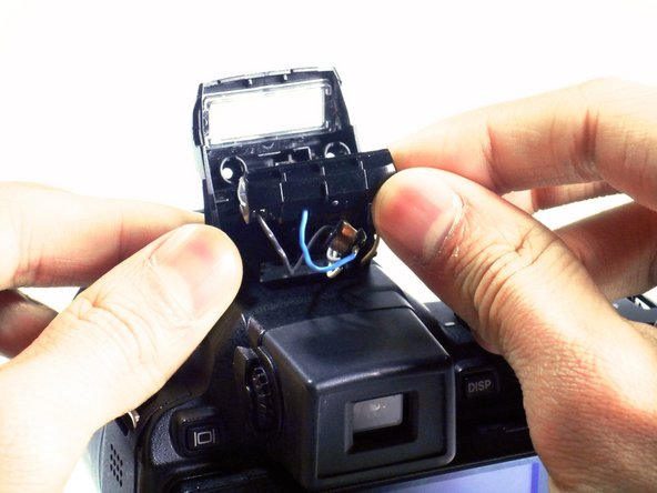 Carefully remove the flash bulb holder with your fingers.