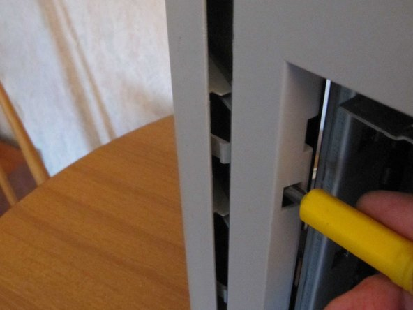 Release the rear top cover. This is secured by 5 clips, the middle 3 of which can be released by inserting a flat screwdriver in the holes underneath them. The other 2 can be popped out quite easily.