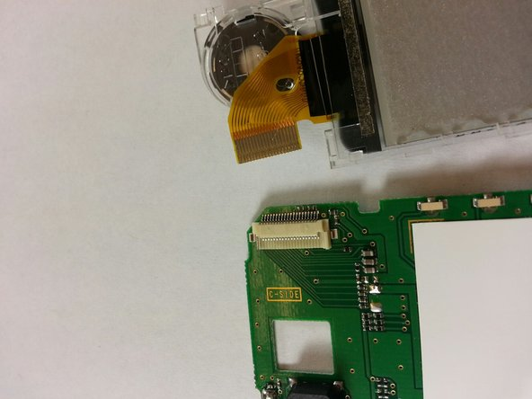 Place the ribbon of the new screen into the clip on the top right of the circuit board.