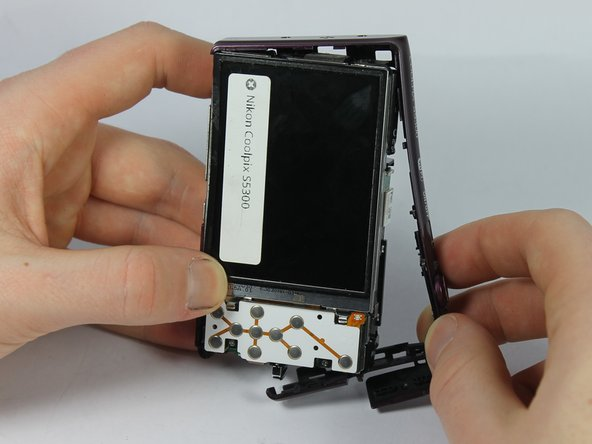 Carefully remove the top button casing by pulling it away from main camera.