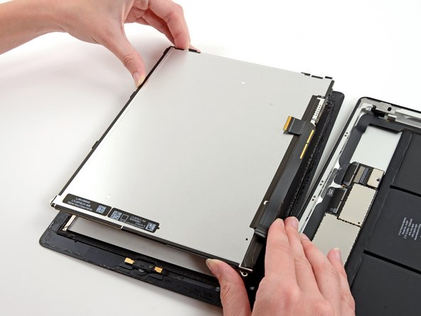 Without touching the front of the LCD, lift the LCD off the front panel.