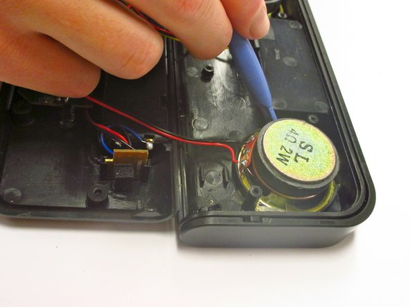 Using a plastic tool, scrape the glue from around the speakers