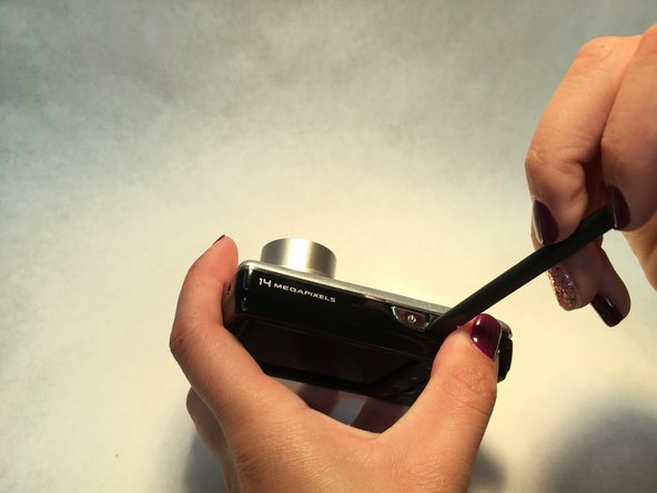 Inserting the prying tool as shown, gently separate the front and back pieces of the camera exterior.